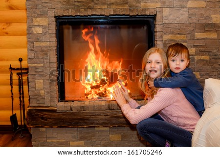 Brother and sister sitting near the fireplace - stock photo