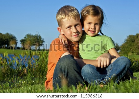 Brother and sister sitting on grass - stock photo