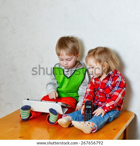 Brother and sister sitting on kitchen table. Little cute girl holding in her hands a radiotelephone and boy holding tablet computer. Children looking at the screen of tablet. Love, Family, Friendship - stock photo