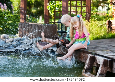 brother and sister sitting on the wooden bridge and dangling  legs in the water