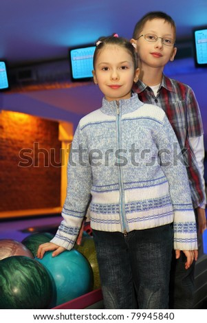 Brother and sister stand alongside near balls for bowling, focus on girl - stock photo