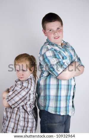 brother and sister standing back to back - stock photo