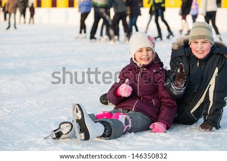 Brother and sister together fell while skating and doing a thumbs up - stock photo