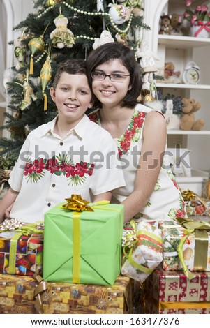 Brother and sister under Christmas tree with gifts - stock photo