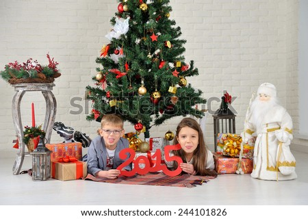 brother and sister under the Christmas tree with gifts - stock photo