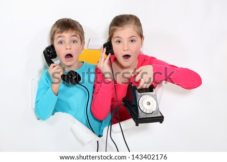 Brother and sister using old telephone - stock photo