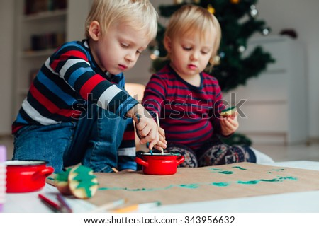 Brother and sister using the brush and color from red pots for Christmas decorations - stock photo
