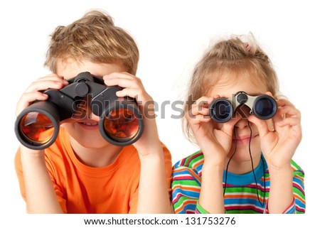 Brother and sister watching through binoculars on a white background - stock photo