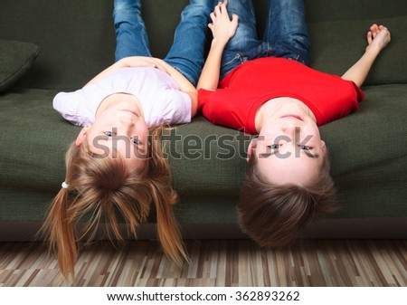 Brother and sister  wearing casual clothes  laying upside down on a green sofa at home smiling - stock photo