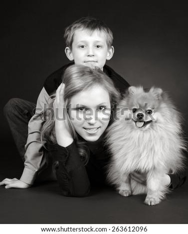 Brother and sister with a dog on black - stock photo