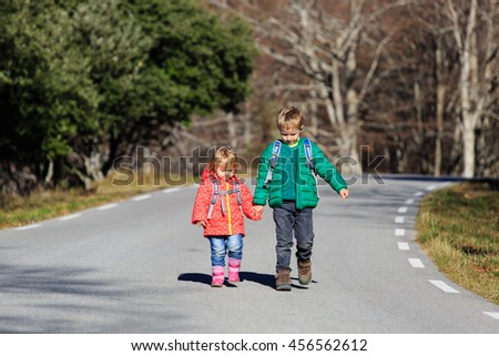 brother and sister with backpacks walking on the road - stock photo