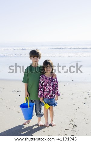 Brother and Sister with Bucket Standing on the Beach