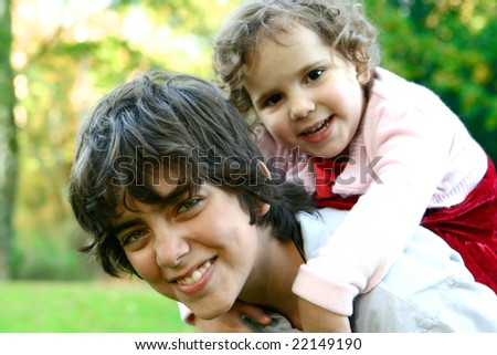 Brother carrying his little sister on his back, enjoying the outdoor - stock photo