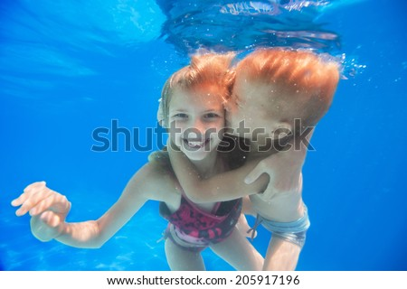 brother hugs and kisses his sister under water - stock photo