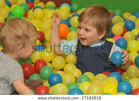 brother kids playing with colored balls - stock photo