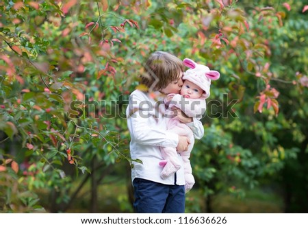 Brother kissing his baby sister under a colorful autumn tree - stock photo