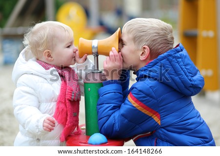 Brother teenager boy and little toddler sister playing together at the playground - stock photo