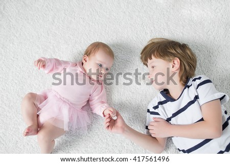 Brother Toddler with baby sister lying on the floor in the nursery. - stock photo