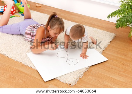 Brother watching his sister drawing on white sheet in the room