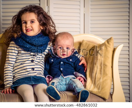 brother with sister on a beautiful sofa with pillows, dressed in stylish clothes