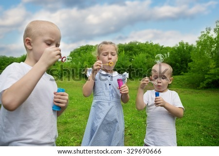 Brothers and sister are inflated bubbles in the summer park - stock photo