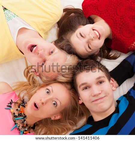 Brothers and sisters lying on a floor together - stock photo
