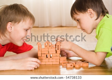 brothers are building on the floor of a toy castle - stock photo