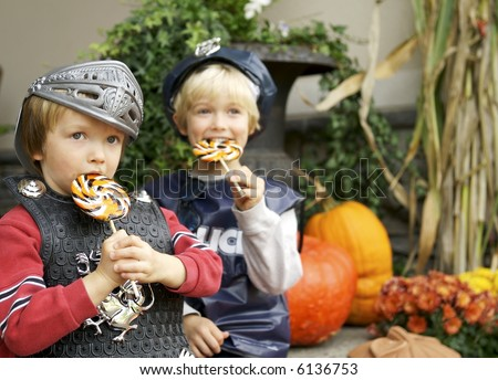Brothers eating suckers they got trick or treating, focus on  knight with policeman blurred - stock photo