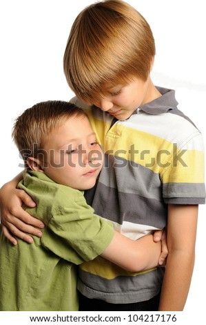 Brothers Hugging. A seven-year old and nine-year old boy hugging each other. - stock photo