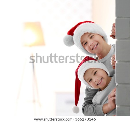 Brothers in Santa hats look out through a brick wall - stock photo