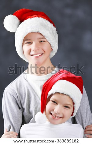 Brothers in Santa hats on grey background