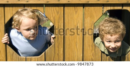 Brothers looking out wooden holes while outdoors - stock photo