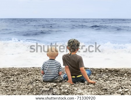 Brothers on a beach. - stock photo