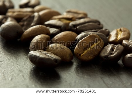 Brown and black coffee beans on dark background