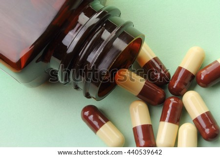Brown and cream medicinal capsules spilling from a medicine bottle