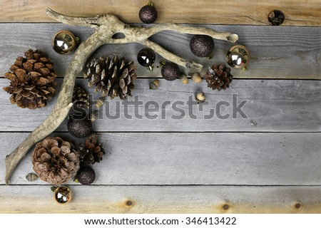 Brown and gold sparkly christmas tree bulb decorations, pine cones, and acorns frame a background of weathered old barn wood. - stock photo