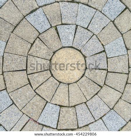 Brown and gray tiled floor in circular shape, an abstract pattern.