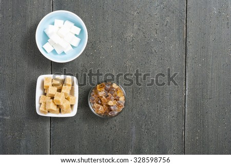 brown and white cubes and rock sugar, dark wood table - stock photo