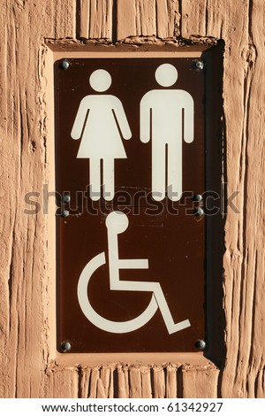 brown and white disabled bathroom sign on a forest service outhouse