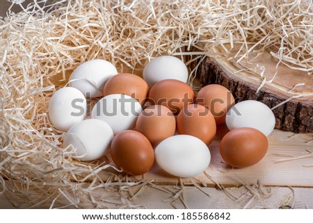 Brown and white eggs in the straw nest on wooden background - stock photo