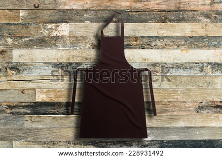 Brown apron against vintage wooden background - stock photo