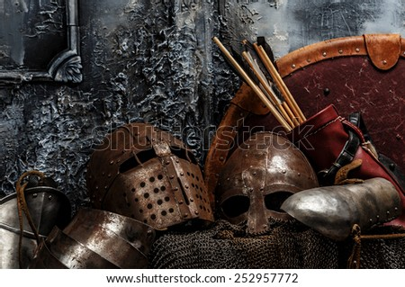 Brown armours. Two helmets, arrows, shield and armours on grey background. - stock photo