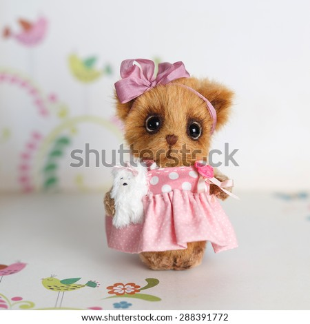 Brown artist Teddy bear in pink clothes with white dog - stock photo