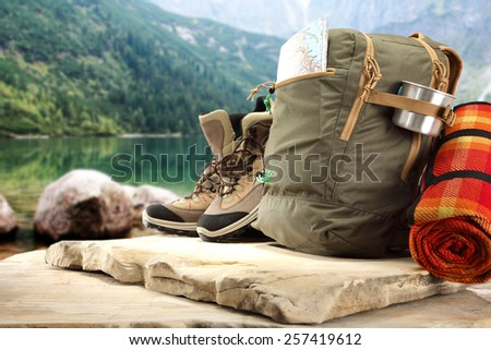 brown backpack on stone and lake landscape  - stock photo
