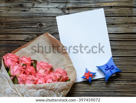 Brown bag of multiple pink stemmed roses with blank white paper and blue star shaped gift box over weathered wooden background - stock photo