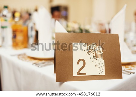 Brown board with the number of the wedding table - stock photo