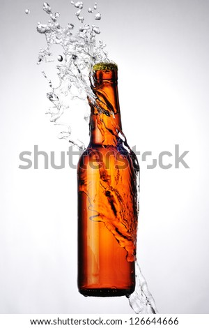 Brown bottle of beer and a water splash