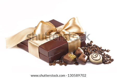 brown box with candies and golden tape, coffee grains on a white background - stock photo