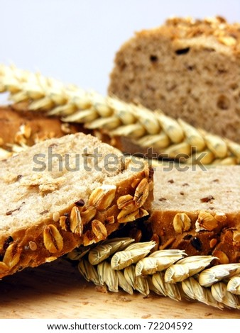 Brown bread & wheat on a wooden board - stock photo