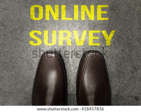 Brown business shoes on floor with text:Online survey - stock photo